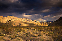 A storm passes by at sunset in the Last Chance Range, Death Valley National Park, California, USA