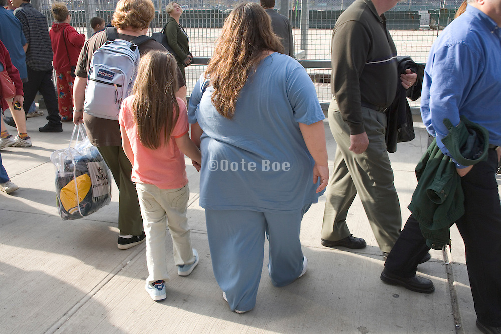 a very obese mother with daughter walking