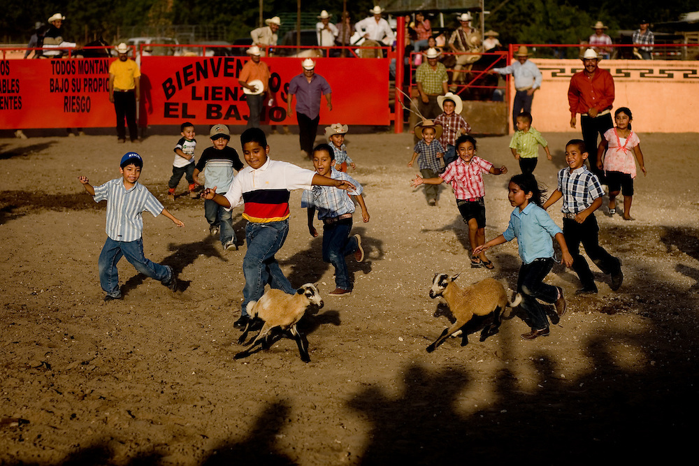 Children race to be the first to catch a goat during a break from bull riding at El Bajio in Von Ormy, Texas.