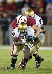 November 28, 2009; Stanford, CA, USA; Notre Dame Fighting Irish running back Robert Hughes (33) is tackled by Stanford Cardinal defensive end Tom Keiser (94) during the first quarter at Stanford Stadium.  Stanford defeated Notre Dame 45-38.