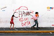 APOIO A HUGO CHÁVES CARACAS -  02/01/2013 .INTERNACIONAL -  Família passa por grafite em muro da cidade de Caracas com frase de apoio ao Presidente Hugo Cháves, que foi operado em Cuba em dezembro último em decorrência de um câncer.  FOTO: DANIEL GUIMARÃES/FRAME