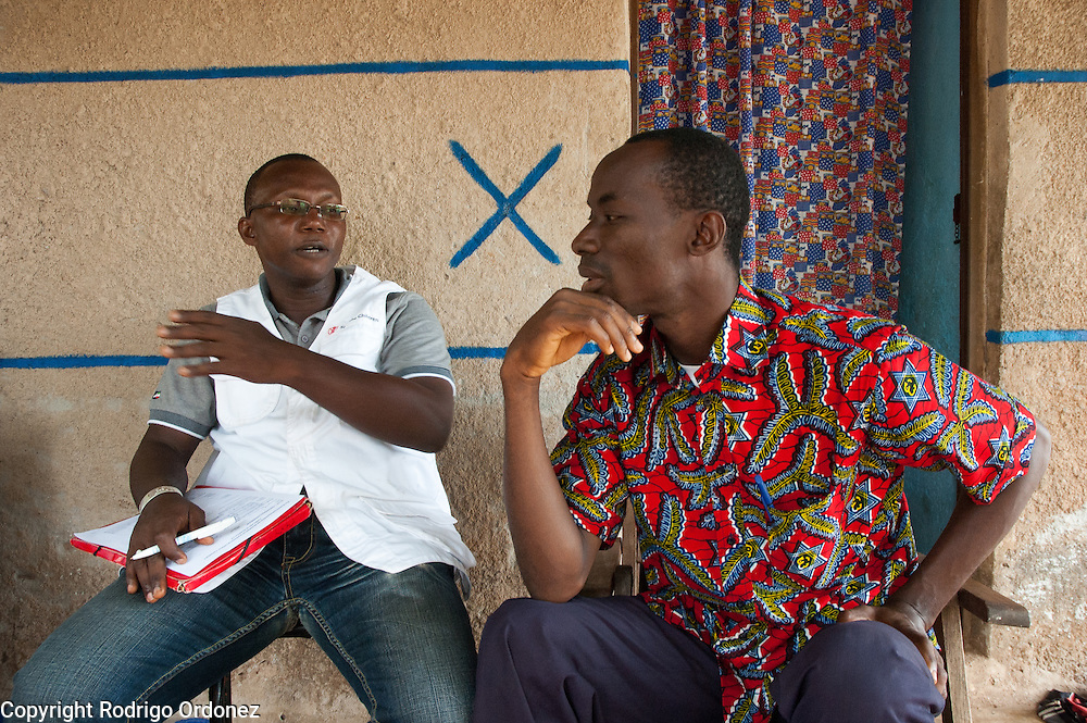 A Save the Children staff member (left) talks to Maimouna's father Toumari, 38, at the family's home in Du&eacute;kou&eacute;, western C&ocirc;te d'Ivoire.<br /> Maimouna had been separated from her family for three months, since the moment armed conflict broke out in her hometown, Du&eacute;kou&eacute;, and she had to flee to Man. Save the Children facilitated the reunion with her parents and her return home.