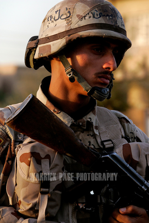 IRAQ, BAGHDAD - JUNE 25: An Iraqi soldier conducts a patrol with a US Army scout platoon, June 25, 2008 in Baghdad, Iraq.  Neighbourhoods like Sadiyah became a battleground for Shiite militias and Sunni extremists after the bombing of the Golden Mosque in Samarra in 2006. Tens of thousands of people were either forced out of their homes or fled the violence to neigbouring countries or other parts of Iraq. Now predominantly Shiite, Sadiyah is being used as a test case by the Iraqi government to encourage the millions who have fled - many of which have the skills and money to rebuild the country. Since early 2008, Iraq's security situation has improved with oil production is increasing, record government surplus and easing sectarian tensions. (Photo by Warrick Page)
