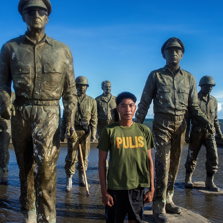 Rexon (28), a police officer, poses next to the statue of General Macarthur at the landing site shrine.