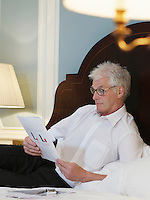 Man lying on bed reading document