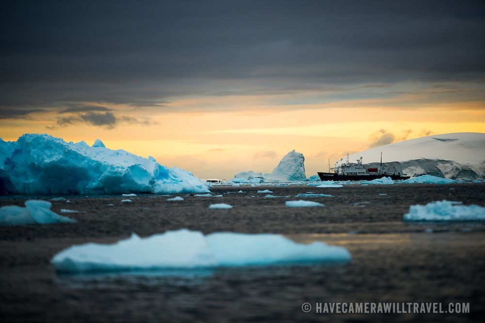 A scenic Antarctic sunset, with a cruise ship in the distance past the brash ice and small icebergs, as the setting sun casts a golden glow on the horizon.