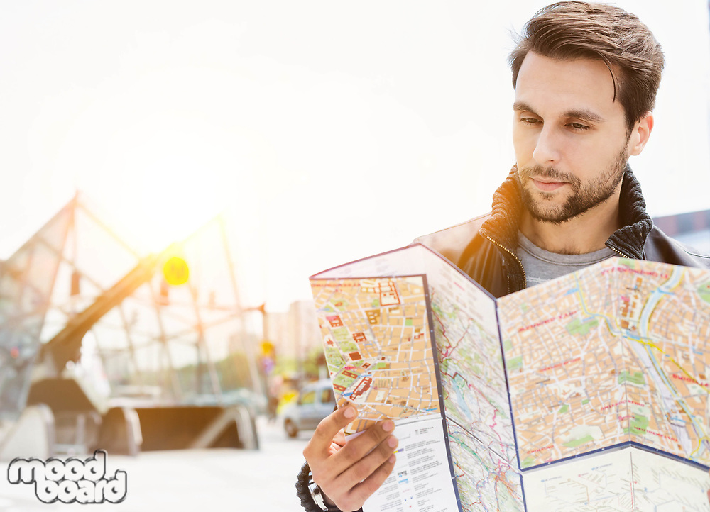 Portrait of young attractive man looking on the map in the city with lens flare in background