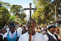 Ricardo Joseph, 18, carries the cross to lead an annual procession of local church goers through the town of Milot, Haiti, on the eve of Ash Wednesday February 16, 2010.  Hundreds of faithful walked for hours in the midday sun singing praises to God and praying for Haiti.