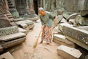 19 MARCH 2006 - SIEM REAP, SIEM REAP, CAMBODIA: A Buddhist nun sweeps the dirt floor in the Preah Khan temple complex within the environs of the Angkor Wat complex. Preah Khan, an 11th century temple built in the Buddhist tradition, is one of the outer temples of the Angkor complex and has not been restored like many of the temples in the Angkor complex.  Photo by Jack Kurtz / ZUMA Press