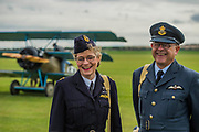 A couple  of Re enactors in uniform in front of the WW1 planes - Duxford Battle of Britain Air Show taking place during IWM (Imperial War Museum) Duxford's centenary year. Duxford's principle role as a Second World War fighter station is celebrated at the Battle of Britain Air Show by more than 40 historic aircraft taking to the skies.