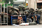 16 MAY 2010 - BANGKOK, THAILAND: Anti government protesters on Rama IV Road take shelter as unidentified snipers open fire on them Sunday. Thai troops and anti government protesters clashed on Rama IV Road again Sunday afternoon in a series of running battles. Troops fired into the air and unidentified snipers shot at pedestrians on the sidewalks. At one point Sunday the government said it was going to impose a curfew only to rescind the announcement hours later. The situation in Bangkok continues to deteriorate as protests spread beyond the area of the Red Shirts stage at Ratchaprasong Intersection. Many protests now involve people who have not been active in the Red Shirt protests and live in the vicinity of Khlong Toei slum and Rama IV Road. Red Shirt leaders have called for a cease fire, but the government indicated that it is going to go ahead with operations to isolate the Red Shirt camp and clear the streets.      PHOTO BY JACK KURTZ