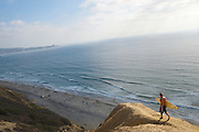Surfer walking the Goat Trail - Blacks Beach - La Jolla - California