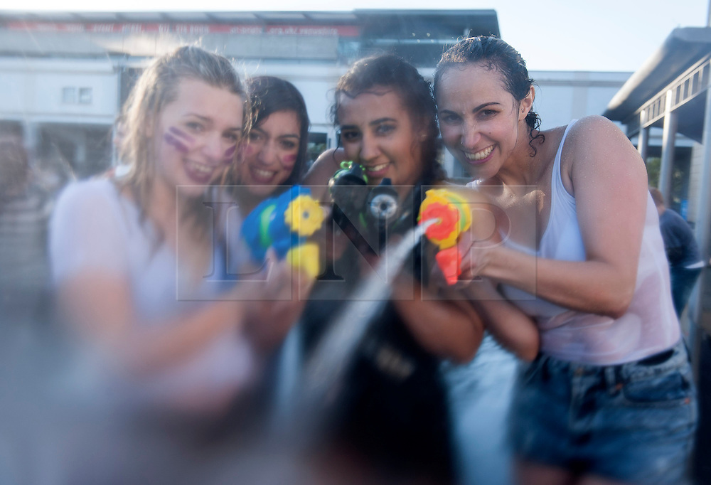 """© Licensed to London News Pictures. 03/06/2015. Bristol, UK.  Left-right: Ala Roszkiewicz age 15, Hanna Coss age 15, Camille Vaz age 16 from Brazil, Angelita Vaz age 35 from Brazil. Giant water fight in Bristol's Millennium Square, organised by The Smile Instigation Collective, a group who say they are dedicated to """"infecting people with happy"""".   It is to celebrate the last session of the Smile Instigation Collective and includes decorating the fountains at Millennium Square with recycled flowers.  Photo credit : Simon Chapman/LNP"""
