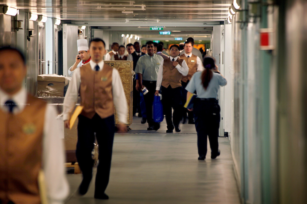 Crew milling around in the service corridors on the lower decks onboard the cruise ship Oasis of the Seas. The ship, currently the largest in the world, is owned by Royal Carribean Cruise Line.