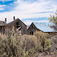 The ruins of a derelict homestead stand empty in a landscape covered in sagebrush in Southern Oregon.