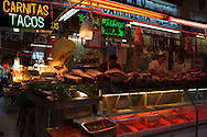 A row of butchers sell fresh cut meats (pork or beef), house made sausages or chichcharron (fried pork skin, left below neon 'carnitas' sign).