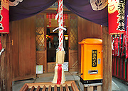 The orange box is an automated fortune telling machine. This image was taken at a small hidden away Fox Shinto Shrine in Tokyo. The shrine is tucked away between large buildings.