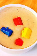 Colourful monopoly houses sinking in a cup of cappuccino; representing negative equity in the once buoyant housing market.