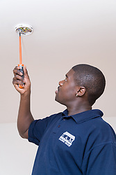 Electrician fixing a smoke detector into the ceiling,