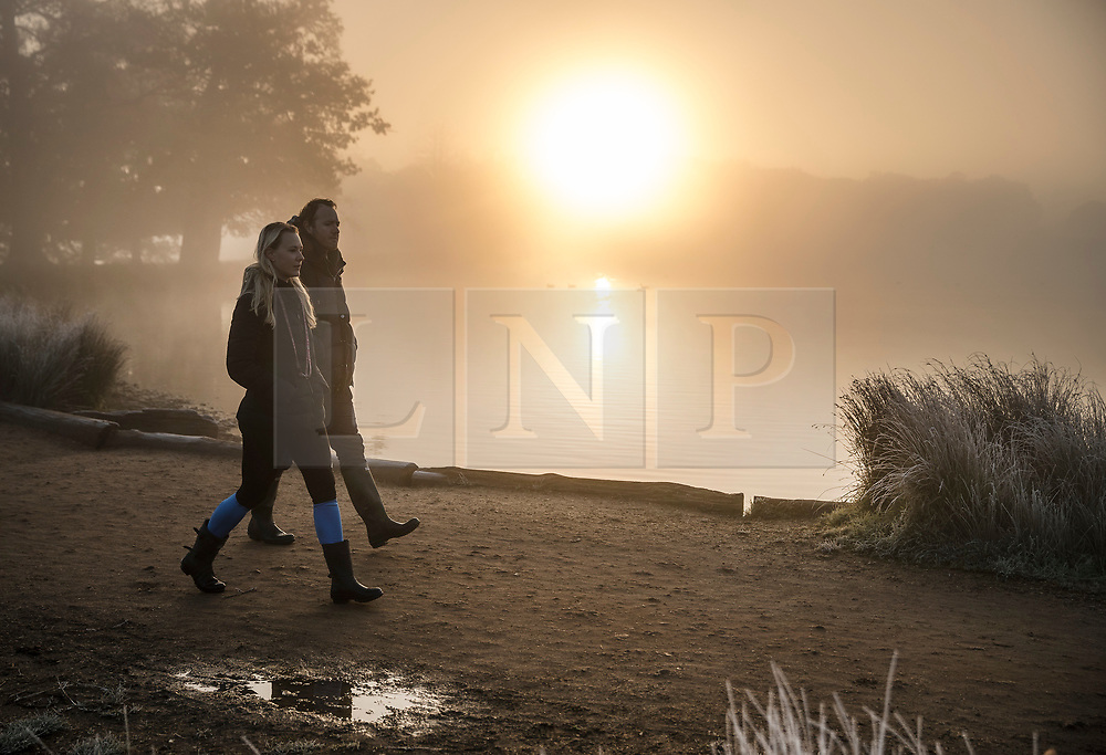 © Licensed to London News Pictures. 06/11/2017. London, UK. A couple walk past Pen Ponds in Richmond Park at first light. Parts of the UK are experiencing freezing temperatures today. Photo credit: Peter Macdiarmid/LNP