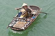 Vendor in her boat, selling shells to tourists on Halong Bay, Vietnam.