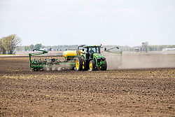 A farmer maneuvers a large tractor through a field pulling a planting implement