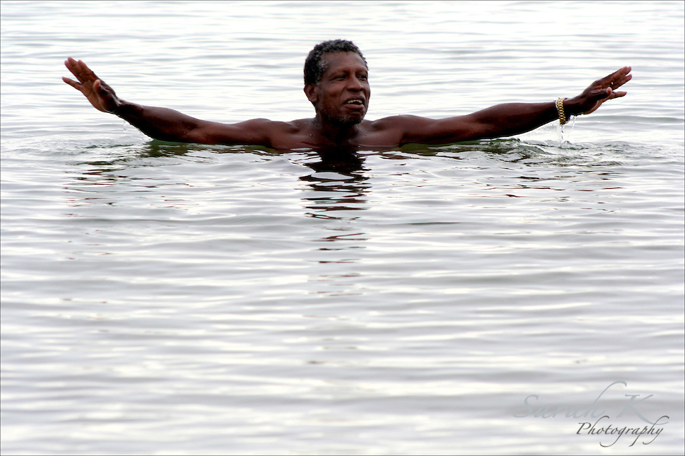 Fisherman Thomas ìTurkeyî Nunez swims in the sea to cool off in the middle of the day. After living in Chicago for 28 years, he missed Belize enough to return.