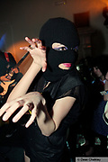 A girl wearing a balaclava, making a claw with her hands, posing, Southend, UK 2006