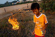 Boys start small fires in the dry grass that has grown on the sand that was used to fill in Boeung Kak Lake, once Phnom Penh's largest freshwater lake.