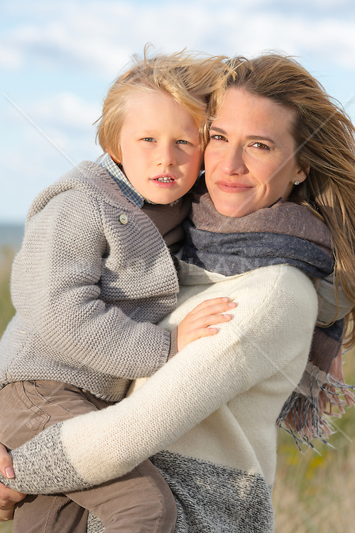 mother holding her young son outdoors in The Fall