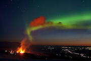 Aurora Borealis in the sky behind the erupting volcano in Fimmvörðuháls, south Iceland 2010
