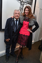 TERRY O'NEILL and CHRISTINA ESTRADA JUFFALI at a private view of photographs 'Terry O'Neill-The Best Of' held at The Little Black Gallery, 13A Park Walk, London on 16th January 2014.