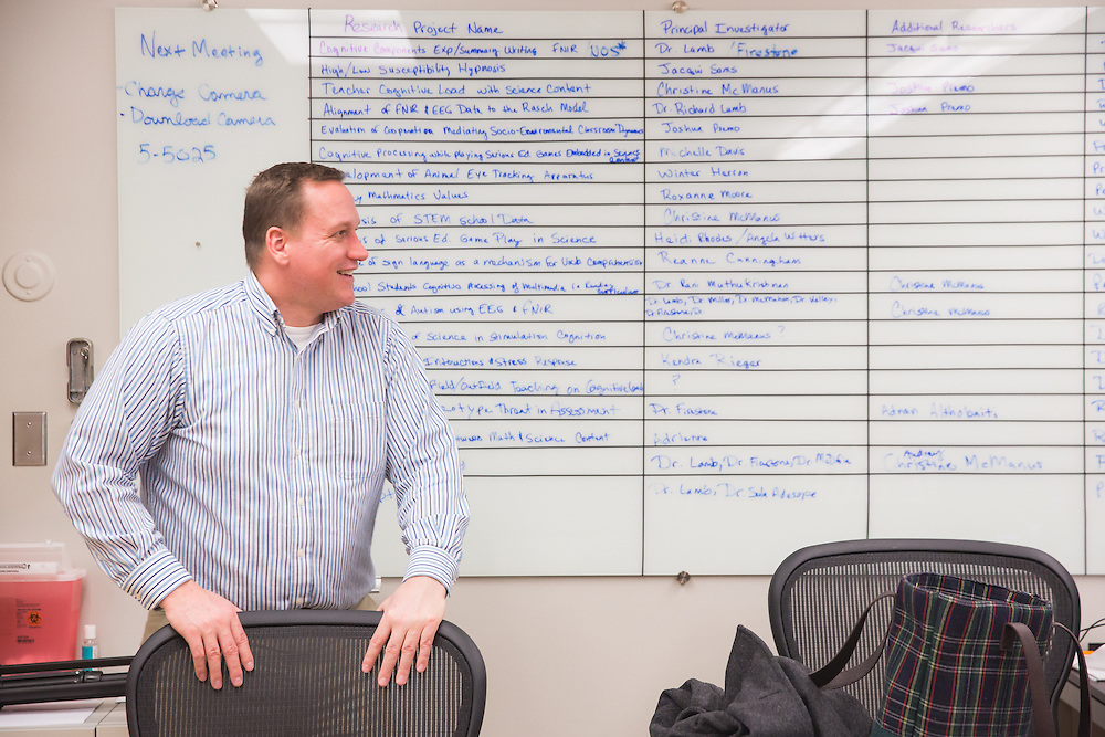 "Dr. Richard Lamb, associate professor of science education measurement at Washington State University, relaxes at the end of the day in front of ""the board"" which highlights the different research projects associated with the neurocognition science lab he leads."
