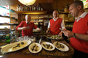 Alla Rivetta, a traditional restaurant and lunch break for the Gondolieri. The boss (l.) serving artichokes.
