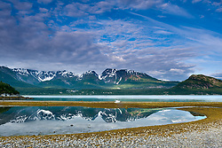 "Red Mountain is reflected in a low tide tidal pool on the beach at Wolf Point on the Muir Inlet in Glacier Bay National Park and Preserve in southeast Alaska. Also pictured at far right is ""The Nunatak, a glaciated knob."
