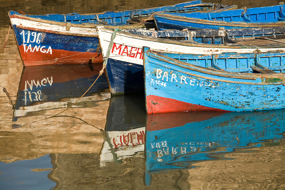 Three fishing boats and their reflections as they are moored in the harbor of Essaouira, Morocco.