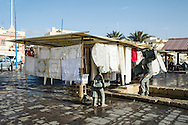 One of the many market stalls that line the harbour of Marsaxlokk is almost set up on top of a sculpture celebrating the fishing history of the village