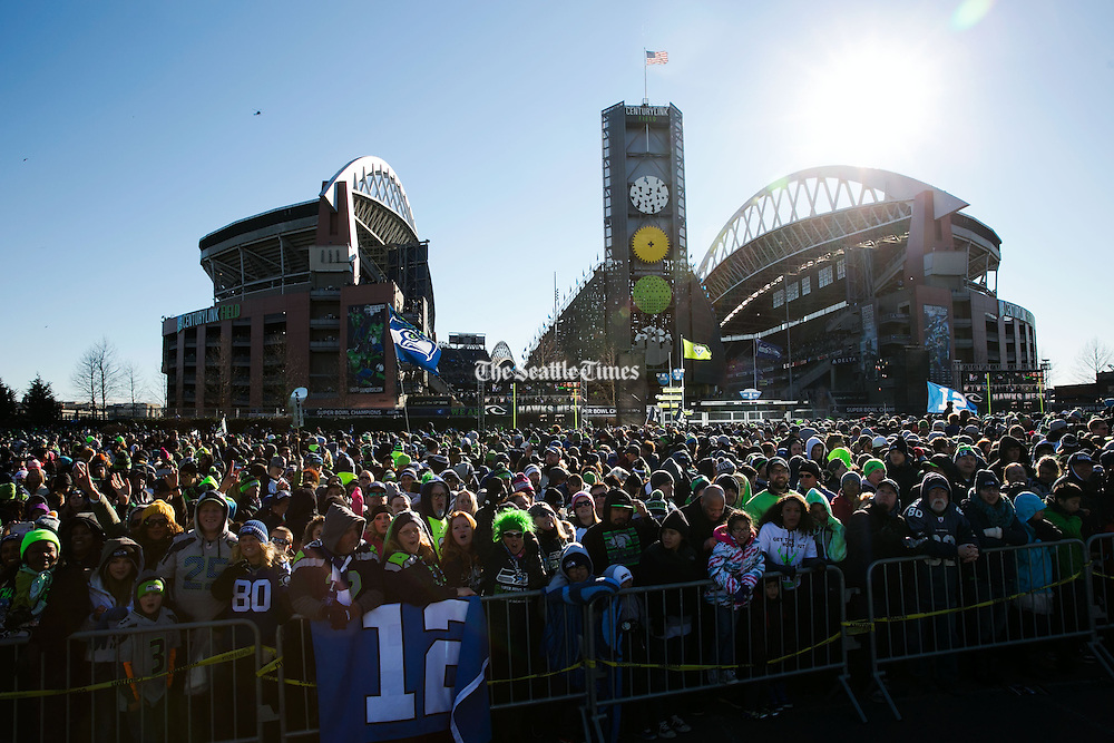 Seahawks fans gather outside CenturyLink Field to watch the Super Bowl parade go by before heading into the Seahawks team rally in Seattle, on Wednesday, Feb. 5, 2014. <br />