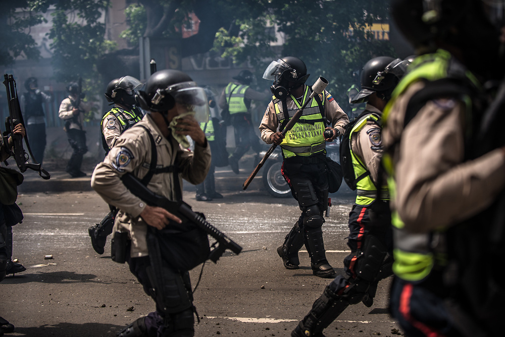CARACAS, VENEZUELA - MAY 24, 2017: Members of the National Police run with crowd control weapons that launch tear gas, after anti-government protesters. The streets of Caracas and other cities across Venezuela have been filled with tens of thousands of demonstrators for nearly 100 days of massive protests, held since April 1st. Protesters are enraged at the government for becoming an increasingly repressive, authoritarian regime that has delayed elections, used armed government loyalist to threaten dissidents, called for the Constitution to be re-written to favor them, jailed and tortured protesters and members of the political opposition, and whose corruption and failed economic policy has caused the current economic crisis that has led to widespread food and medicine shortages across the country.  Independent local media report nearly 100 people have been killed during protests and protest-related riots and looting.  The government currently only officially reports 75 deaths.  Over 2,000 people have been injured, and over 3,000 protesters have been detained by authorities.  PHOTO: Meridith Kohut