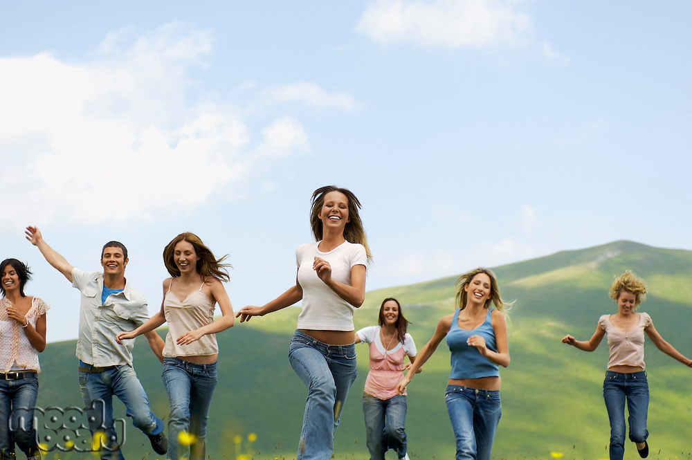 Group of friends running through mountain field front view