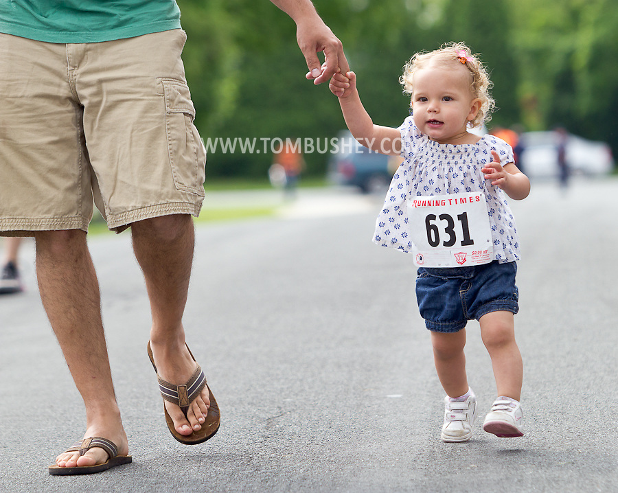 Middletown, New York - A very young girl holds her father's hand while running in the Kids Dash at the 16th annual Ruthie Dino-Marshall 5K Run/Walk hosted by the Middletown YMCA on Sunday, June 10, 2012.Middletown, New York - Runners compete in the 16th annual Ruthie Dino-Marshall 5K Run/Walk put on by the Middletown YMCA on Sunday, June 10, 2012. ©Tom Bushey / The Image Works