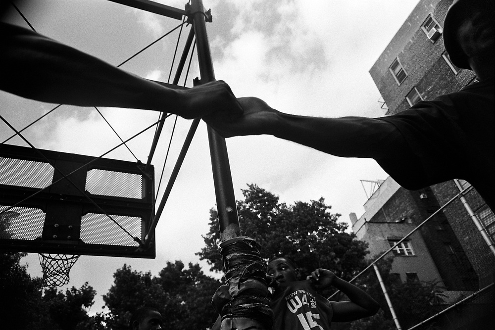 June 15th 2004. New York, New York. United States..Located in the heart of Greenwich Village, the West 4th Street basketball Court, known as ?The Cage?, offers no seating but attracts the best players and a lot of spectators as soon as spring is around the corner..Half the size of a regular basketball court, it creates a fast, high level of play. The more people watch, the more intense the games get. « The Cage » is a free show. Amazing actions, insults and fights sometimes, create tensions among and inside the teams. The strongest impose their rules. Charisma is present..?The Cage? is a microcosm. It?s a meeting point for the African American street culture of New York. Often originally from Jamaica or other islands of the Caribbean, they hang out, talk, joke, laugh, comment the game, smoke? Whether they play or not, they?re here, inside ?The Cage?. Everybody knows everybody, they all greet each other, they shake hands and hug: ?Yo, whasup man??.