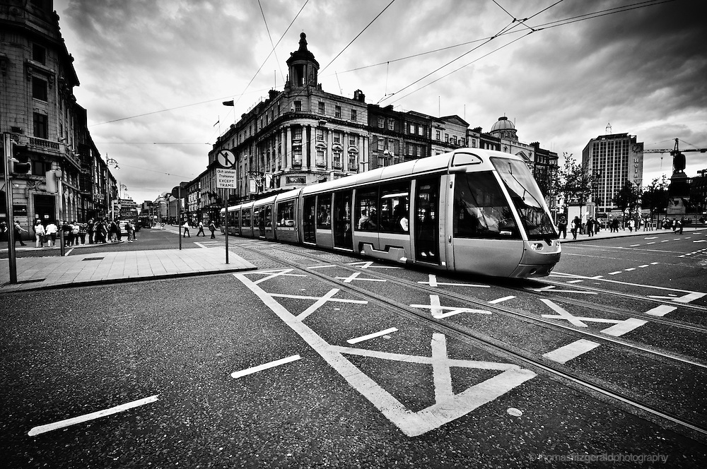 O'Connell Street, Dublin City, Ireland: The Luas Tram crosses the busy O'Connell Street in the heart of Dublin City on a moody and stormy afternoon. Black and White