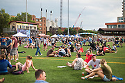 Attendees relax on the turf during the 4th annual Yum Yum Fest held at Breese Stevens Field, Sunday, August 6, 2017.