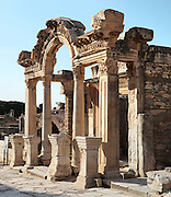 Temple of Hadrian, 2nd century AD, Curetes Street, Ephesus, Izmir, Turkey. The temple was built by Quintilius before 138 AD and was dedicated to the Emperor Hadrian, who came to visit the city from Athens in 128 AD. The colonnade in front of the cella supports a so-called Syrian gable. The reliefs over the door lintel depicting the Ephesian foundation myth were added later. Around 300 AD statues of the emperors Diocletian, Constantius, Maximianus and later Theodosius I were erected, of which inscribed bases are preserved. The facade of the temple has 4 Corinthian style columns supporting a curved arch, in the middle of which contains a relief of Tyche, goddess of victory. The side columns are square. The pedestal with inscriptions in front of the temple, are the bases for the statues of emperors Diocletian, Maximian, Constantius I, and Galerius; the originals of the statues have not been found yet. Ephesus was an ancient Greek city founded in the 10th century BC, and later a major Roman city, on the Ionian coast near present day Selcuk. Picture by Manuel Cohen