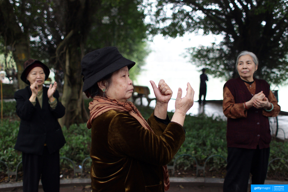 Elderly ladies exercise on a misty morning beside Hoan Kiem Lake, Hanoi, Vietnam.. For a county not know for it's sporting prowess, Hanoi, Vietnam's capital, appears to be gripped in a fitness frenzy. Before 6am street corners, parks and lake sides are a hive of activity as keep fit classes, Tai chi and personal exercise regimes are seen in abundance around the city. Particularly noticeable are Women's keep fit classes, often accompanied by loud poor quality western disco beat music as the occupants of the city get fit come rain or shine. Hanoi, Vietnam. 18th March 2012. Photo Tim Clayton