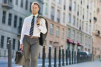 Portrait of mature businessman walking on pavement after work