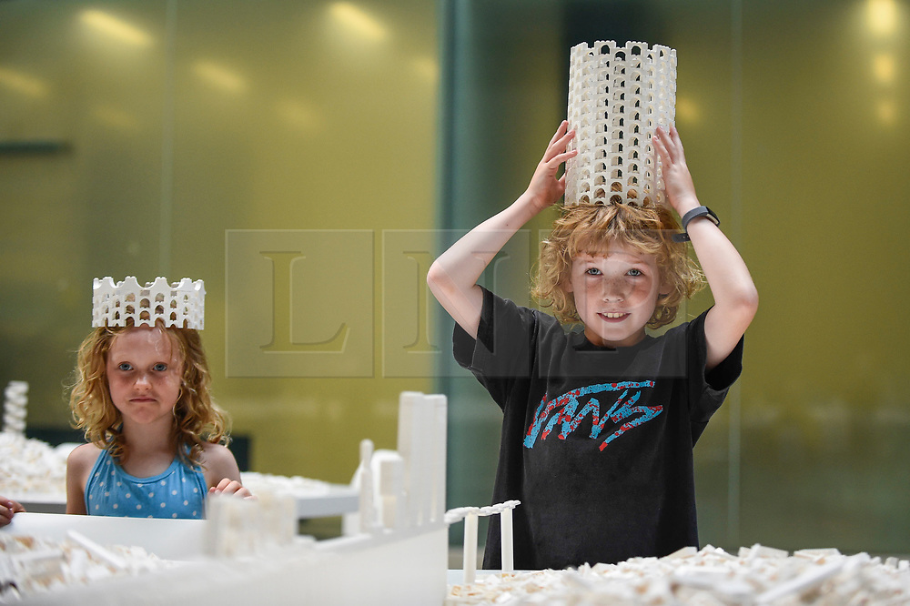 "© Licensed to London News Pictures. 26/07/2019. LONDON, UK. Willow Beal, aged 5 (L), and Hunter Tagholm (R), aged 8, pose with a Lego crown at the preview of ""The cubic structural evolution project"", 2004, by Olafur Eliasson at Tate Modern.  Exhibited for the first time in the UK, the artwork comprises one tonne of white Lego bricks inspiring visitors to create their own architectural vision for a future city and is on display until 18 August 2019.  The work coincides with the artist's new retrospective exhibition ""In real life"" at Tate Modern on display to 5 January 2020. (Parental permission to photograph obtained). Photo credit: Stephen Chung/LNP"