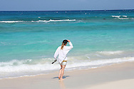 A woman walks along the beach on Stocking Island in the Bahamas