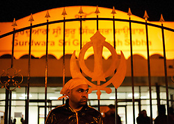 © Licensed to London News Pictures. 10/08/2011. LONDON, UK. Wearing a headscarf a Sikh male stands outside Gurdwara Sri Guru Singh Sabha, part of the largest Sikh temple in Europe, keeps watch for possible trouble. Organised, and coordinating with police, members of Southall's Sikh community come out in force to prevent any rioting from taking place in the area. The vigilante action took place as a fourth night of riots and looting were expected to take place in London. Photo credit: Matt Cetti-Roberts/LNP